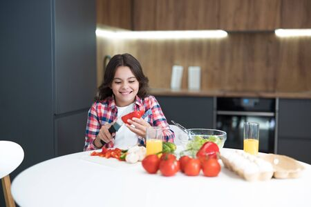 cute teen daughter helping to cook breakfast in the kitchen looking happy