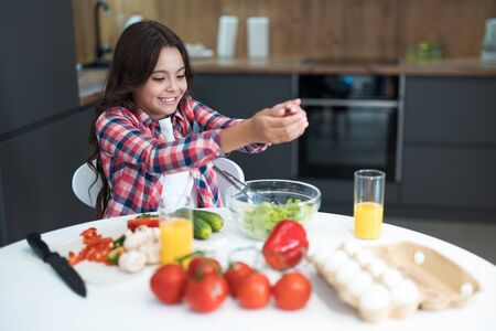 cute teen daughter helping to prepare salad for breakfast in the kitchen looking happy