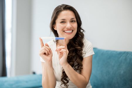 young beautiful woman sits on the sofa holding pregnancy test feeling happy