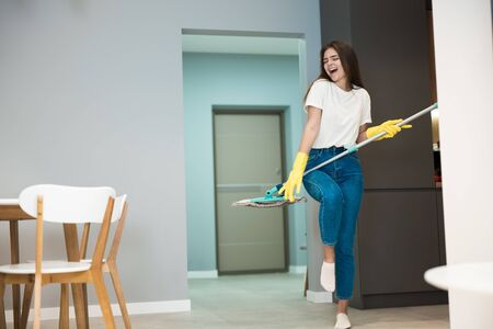 funny young woman in yellow gloves dancing with the mop and singing while washing kitchen floor feeling happy pretending to be rock star