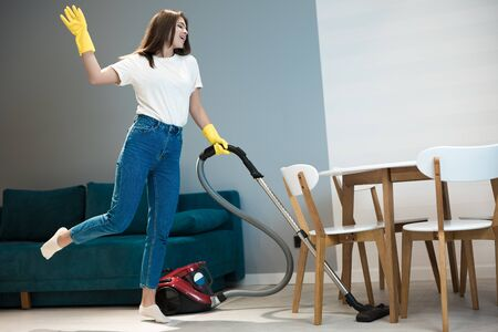 beautiful young woman in yellow gloves dancing while doing vacuum cleaning in the living room