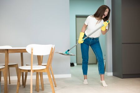 cute young woman in yellow gloves sings holding mop as a microphone while washing kitchen floor plays rock star