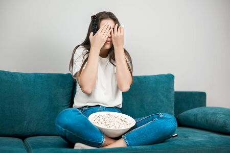 beautiful young woman closes her eyes while watching scary movie on the sofa eating popcorn feeling comfortable on the sofa at home looking frightened Stock fotó