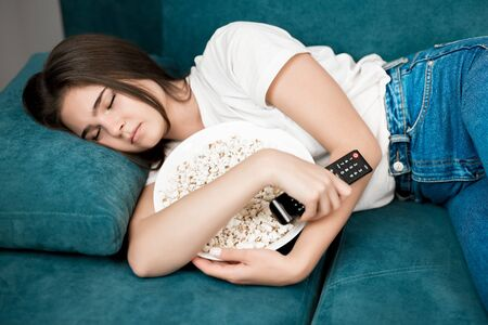 young woman fall asleep on the sofa while watching TV in the living room with remote control in one hand and popcorn in another Stock fotó
