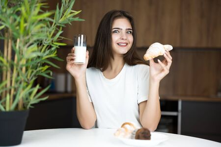 beautiful young smiling woman feeling hungry holding croissant and glass of kefir for breakfast in the kitchen looking happy eating