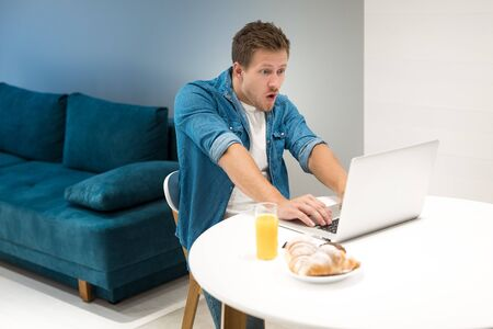 young handsome man working in his laptop from home while having croissant and fresh orange juice for lunch looking surprised