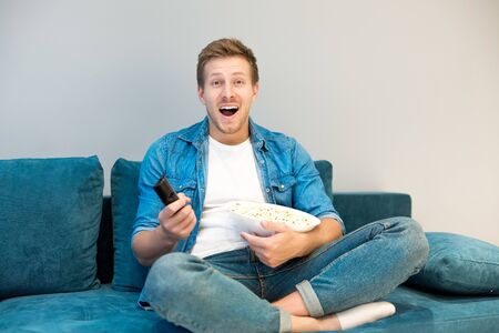 young handsome man watching comedy movie on the sofa eating popcorn feeling comfortable at home laughing