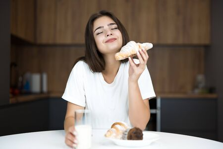 beautiful young smiling woman feeling hungry holding croissant and glass of milk for breakfast in the kitchen enjoying bakery smell