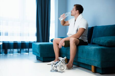 young handsome man drinking water from the bottle during workout at home live sporty