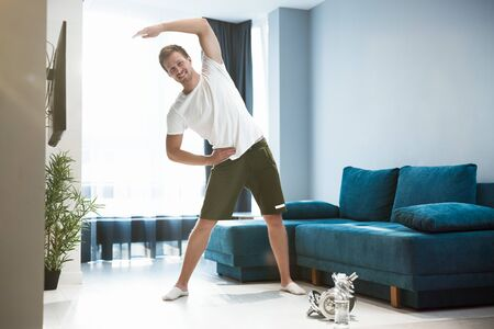 young handsome man doing sideways during warm up before workout at home looking satisfied sporty and healthy lifestyle