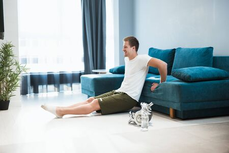 young handsome smiling man sitting on the floor having rest during workout at home looking pleased sporty and healthy lifestyle Zdjęcie Seryjne