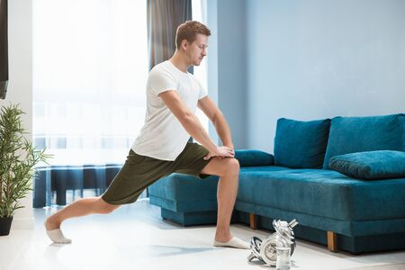 young handsome man doing lunges during stretching before workout at home looking focused sporty and healthy lifestyle