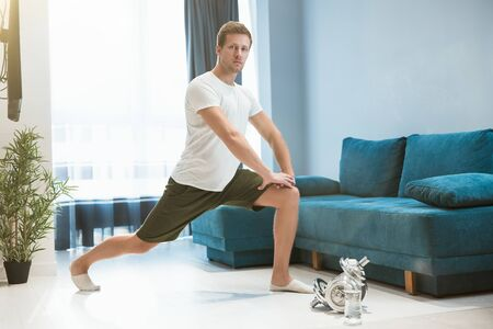 young handsome man doing lunges during stretching before workout at home looking happy sporty and healthy lifestyle