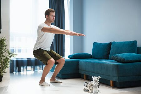 young handsome man doing squats during workout at home looking focused sporty and healthy lifestyle