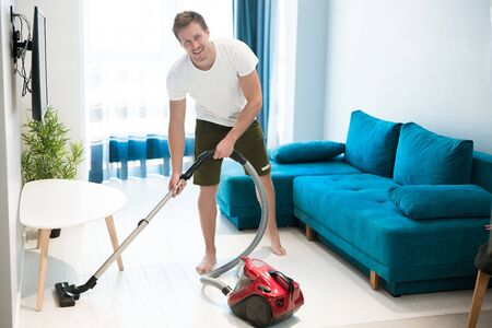 handsome smiling young man doing vacuum cleaning in the living room house chores Zdjęcie Seryjne