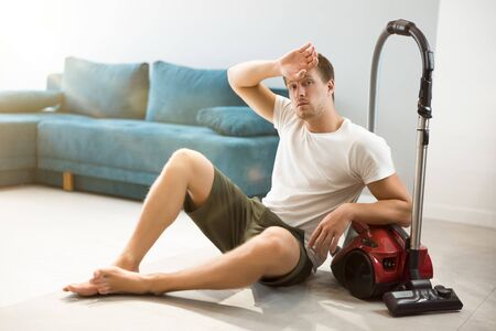 handsome young fatigued man sitting near vacuum cleaner in the living room looking tired after cleaning appartment house chores