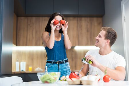 young funny couple cooking breakfast in the kitchen wife holds tomatoes near her eyes jokingly together smiling family traditions