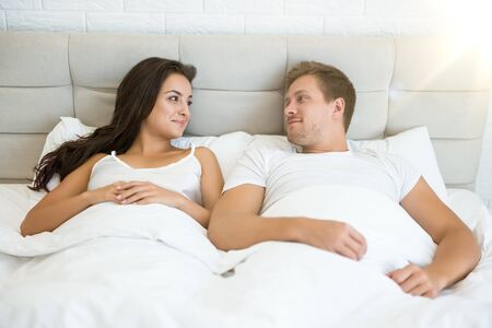 happy young couple handsome man and beautiful woman lying in bed in bright bedroom smiling to each other feeling love family idyll
