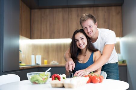 young couple cooking breakfast in the kitchen husband stands behind and hugs his beloved wife while they cut vegetables together smiling family traditions