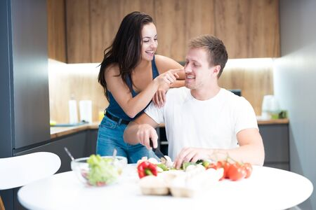 young couple cooking breakfast in the kitchen together wife hugging her beloved husband and touching his nose jokingly family traditions Reklamní fotografie