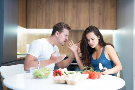 young couple having fight while cooking breakfast in the kitchen husband shouts loud at his wife family quarrel Stock Photo