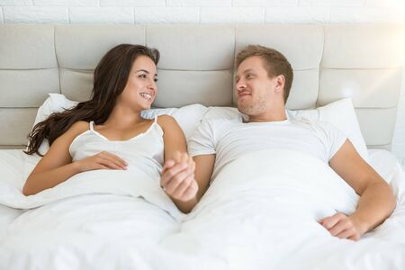 happy young couple handsome man and beautiful woman lying in bed in bright bedroom smiling to each other feeling love family morning idyll