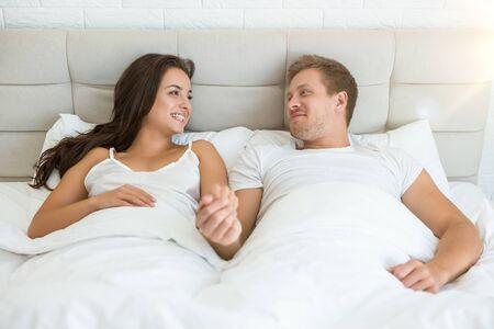 heureux jeune couple bel homme et belle femme allongée dans son lit dans une chambre lumineuse souriant l'un à l'autre sentiment amour famille matin idylle Banque d'images