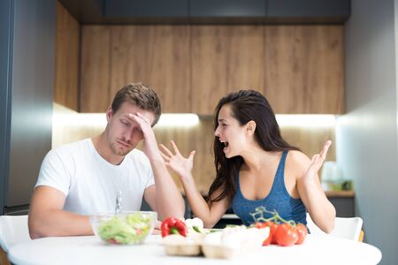 young couple having fight while cooking breakfast in the kitchen wife shouts loud at her husband while he looks annoyed family quarrel Stock Photo