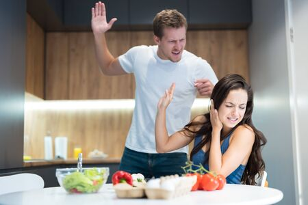 young couple having fight while cooking breakfast in the kitchen husband lifts his arm against his wife while she turns away family vilonce