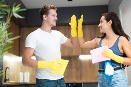 handsome young man giving high five to his beautiful wife wearing yellow gloves while doing cleaning in the kitchen together house chores Zdjęcie Seryjne