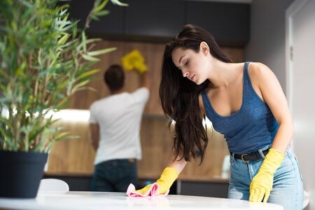 young man thoroughly wiping dust off from the kitchen cabinet with a rag meanwhile beautiful woman wiping kitchen table in yellow gloves doing cleaning together