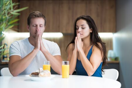 young couple saying prayer before start eating their breakfast in the kitchen family traditions