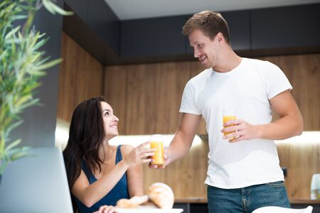 young lovely couple having breakfast man passes his wife glass with orange juice while she works in laptop in kitchen great start of day