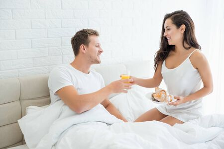 beautiful woman prepared breakfast - croissants and orange juice in bed for her handsome husband looking happy morning family idyll