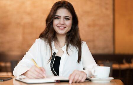 Joven y bella mujer tomando notas para su planificador trabajando fuera de la oficina bebiendo café caliente en la cafetería multitarea moderna empresaria Foto de archivo