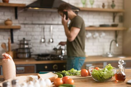 products for breakfast on the table: tomatoe, eggs, oliv oil, cucumber, salad man standing near cooker talking on the phone on blurred background.
