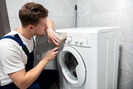 giovane bell'uomo lavoratore in uniforme che ripara la lavatrice a casa nel servizio di riparazione professionale della toilette