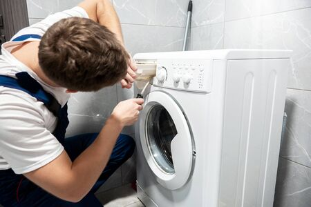 young man worker in uniform repairing washing machine at home in the toilette professional repair service