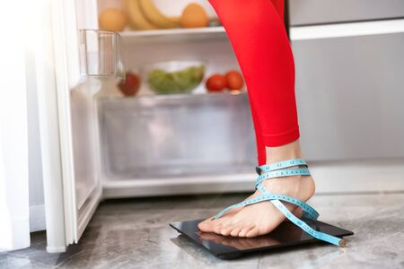 womans legs wrapped in centimeter standing on scales to measure weight in the kitchen near open fridge full of fruits and vegetables, dietology and nutrition