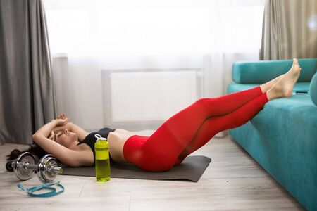 young fit beautiful woman in sportwear lies on the floor looking tired after daily home workout on the mat in living room, sportive lifestyle. 版權商用圖片
