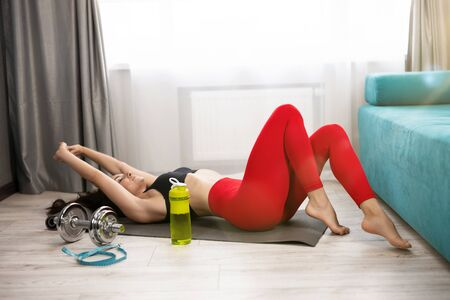 young fit brunette woman in sportwear lies on the floor looking tired after daily home workout on the mat in living room, sportive lifestyle. 版權商用圖片