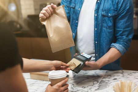 barista man standing behind the bar sells hot coffee drink and lunch in paper bag to woman client for takeaway , woman pays with bank card.