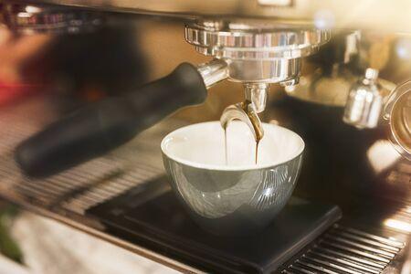 Process of hot coffee drink making using professional coffee machine. Stock Photo