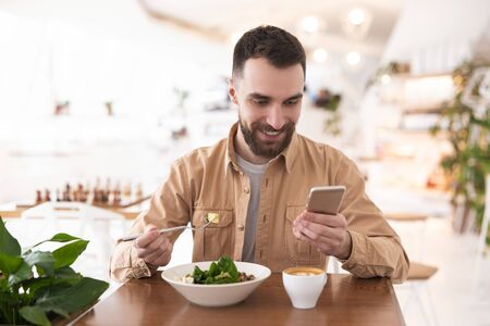 Young bearded smiling man drinks his hot coffee and eats salad for lunch while checking news in his smartphone during break , multitasking concept
