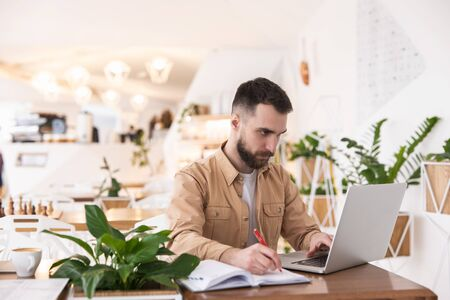 Young handsome bearded man looks concentrated working in laptop taking notes to planner during lunch break at cafe, multitasking concept