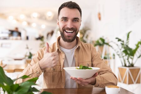 young bearded man holding plate of salad in one hand shows like while eating his lunch in cafe during break, vegan concept