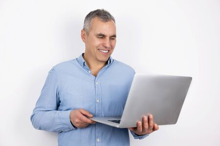 adult handsome man with grey hair wearing blue shirt holds his laptop standing on isolated white background, modern technology concept