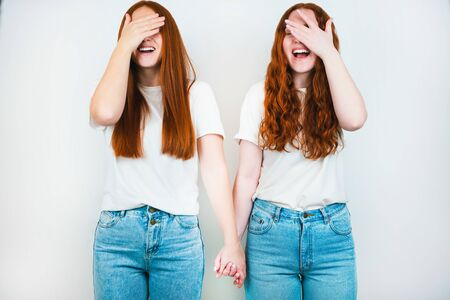 two funny redheaded young women holding standing on isolated white backgroung, one is holding hands, closing their faces with hands, laughing, frienship concept.