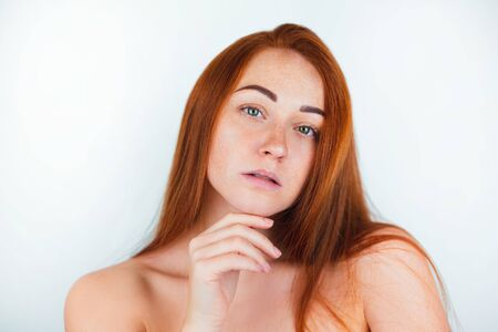 portrait of redheaded young sexy woman looking natural touching her chin with tender on isolated white backgroung, style and beauty concept