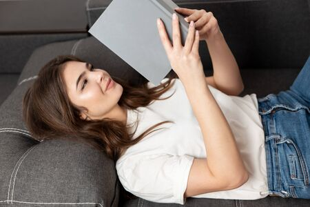 young beautiful brunette woman reading book while lying on the sofa in her appartment, feeling cozy at home